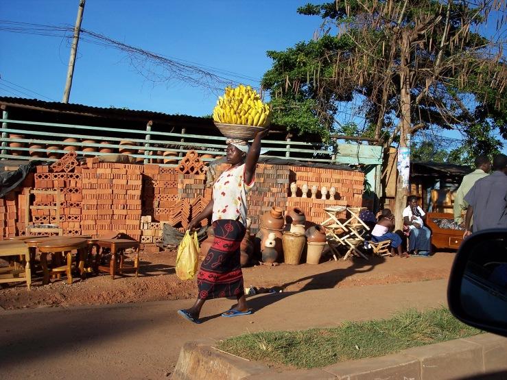 Tomada desde el carro viniendo de Entebbe, una vista típica de las calles de Uganda, la mujer con su carga en la cabeza.